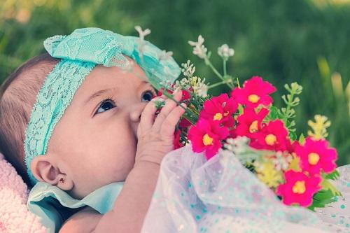 طفلة تلهو ببعض الزهور فى حدائق فيينا